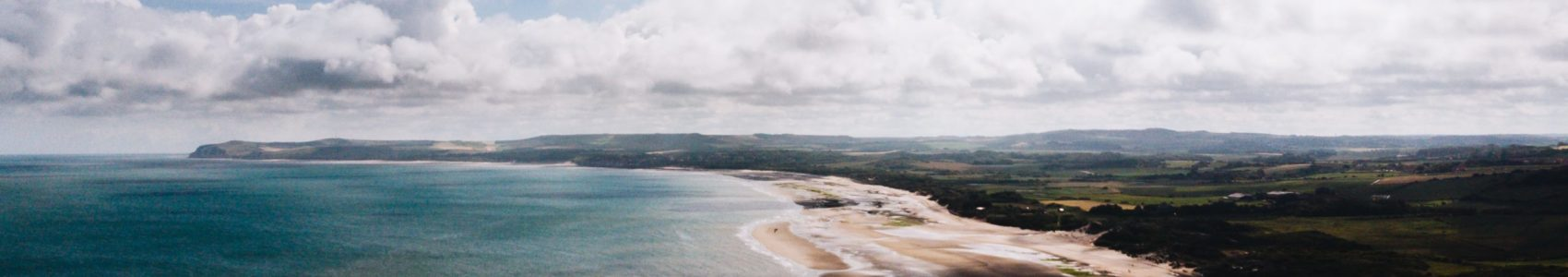 An aerial shot of beautiful beach shore near grassy field with a cloudy sky in the background in France